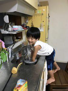 自宅で炊飯ジャーの内釜を洗う息子