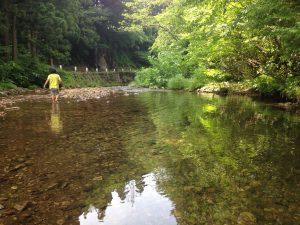 川の浅瀬を歩く息子