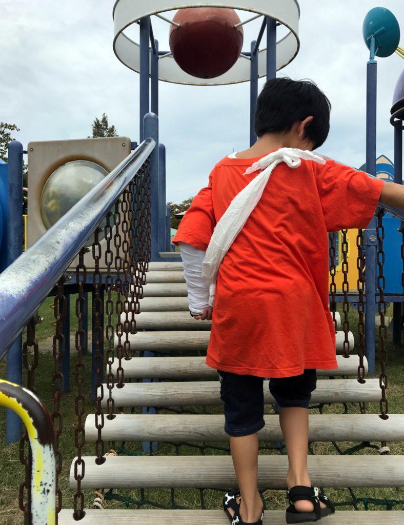 左腕にギプスをしたまま公園で遊ぶ男の子