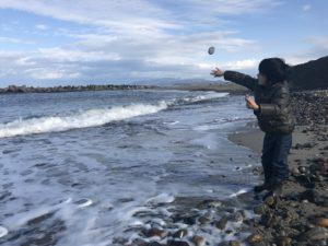 海岸で石を投げる息子