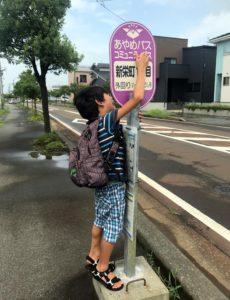 コミュニティーバスのバス停とコミュニケーションを取る息子