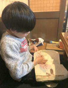義父の焼き鳥店で国語の教科書を音読する息子