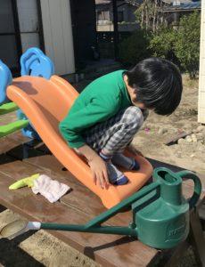家の庭でおもちゃの滑り台で遊ぶ息子