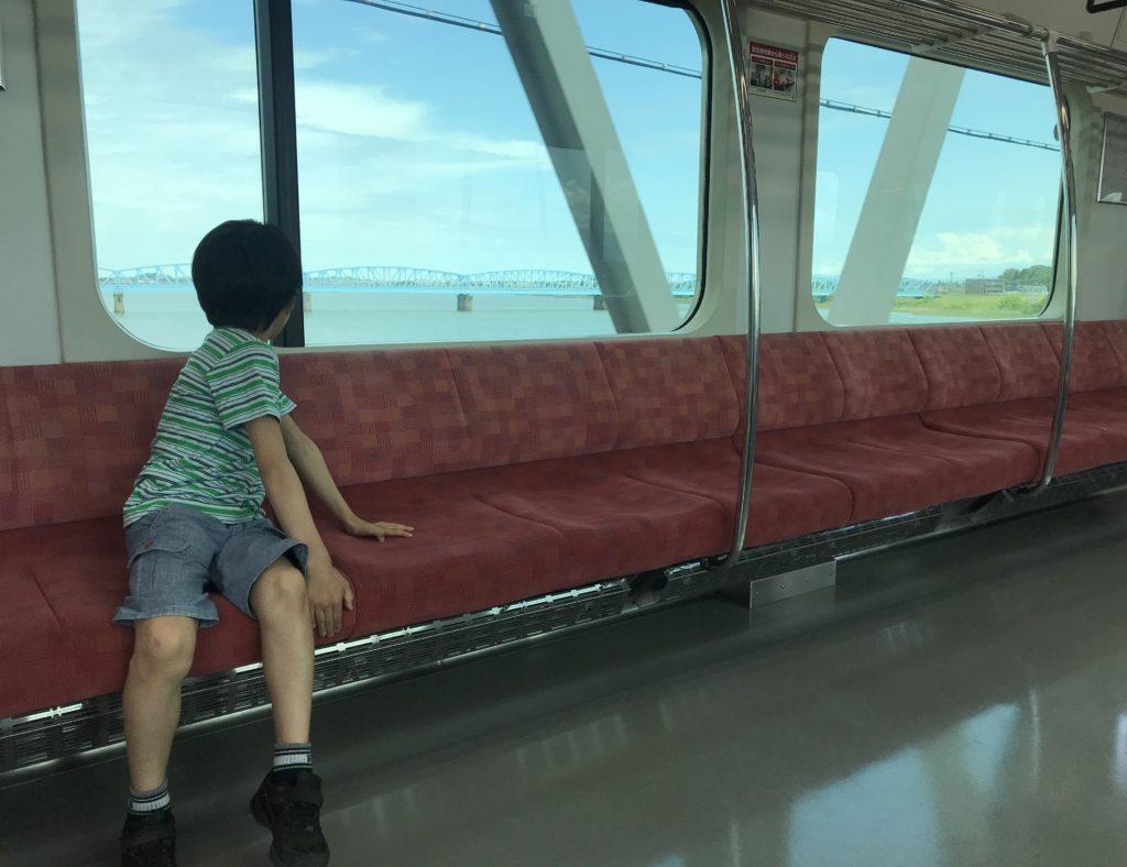 新潟駅に向かう電車に乗る息子。車窓から見えるのは阿賀野川