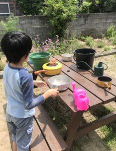 庭のピクニックテービルに水を入れた容器を並べる息子