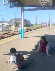 歩き疲れてJR月岡駅ホームに座り込む息子と妻