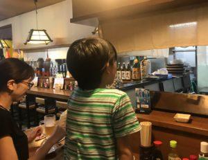 義父の焼き鳥店のカウンターで厨房をのぞき込む息子