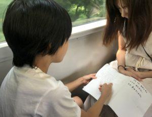 その日の予定が書かれたノートを電車内で眺める息子