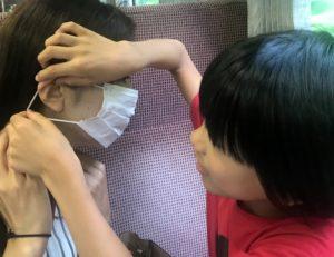 列車内でママにマスクをつける息子