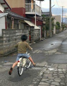 ペダルを使わずに自転車に乗る息子