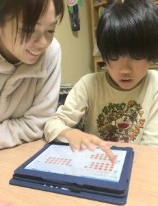 ママと一緒にタブレット端末で算数の勉強をする息子