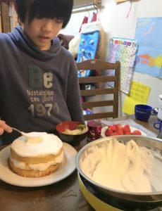 ケーキのスポンジに生クリームを塗る息子