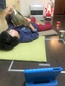 ファンヒーターの前で寝転びながら国語の教科書をみてくつろぐ息子