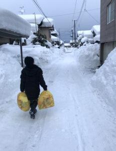 雪道を歩いてゴミ捨てに行く息子