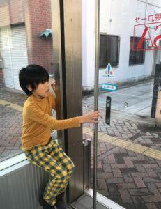 新潟市中央区「西堀ローサ」の地下出入口の自動ドアを開ける息子