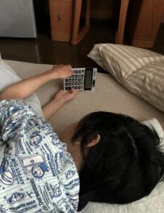 布団に寝転びながら電卓で遊ぶ息子