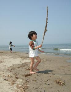 藤塚浜で流木を掲げる息子