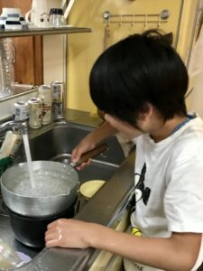 台所で鍋を洗う息子