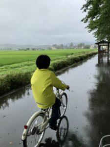 雨の中サイクリングロードを走る息子